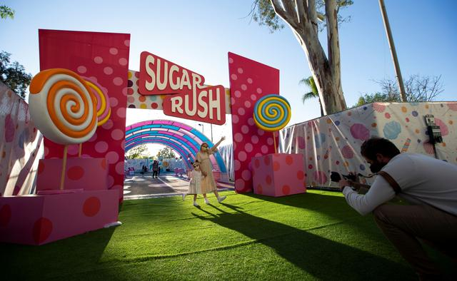 Guests poses for a photo as they enter the ''Sugar Rush'' experience, a candy-based theme park, in Woodland Hills, California, U.S., April 1, 2021.  REUTERS/Mario Anzuoni
