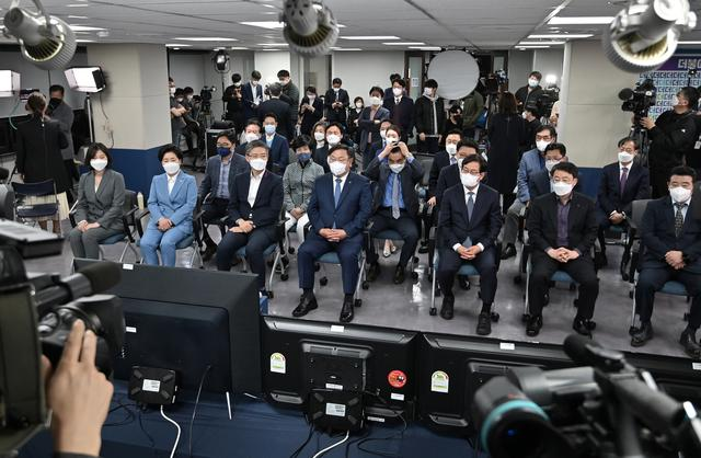 Members of South Korean ruling Democratic Party watch screens showing the result of exit polls of the Seoul mayoral by-election at the party headquarters in Seoul, South Korea April 7, 2021.  Jung Yeon-je/Pool via REUTERS