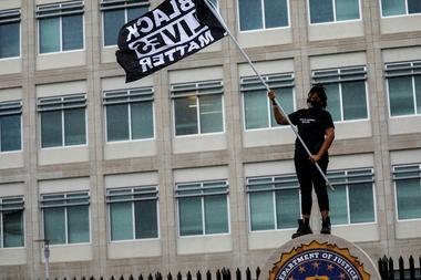 FILE PHOTO: A protester carries a Black Lives Matter flag outside the...