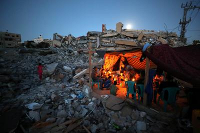 Gazans camp by rubble of their homes