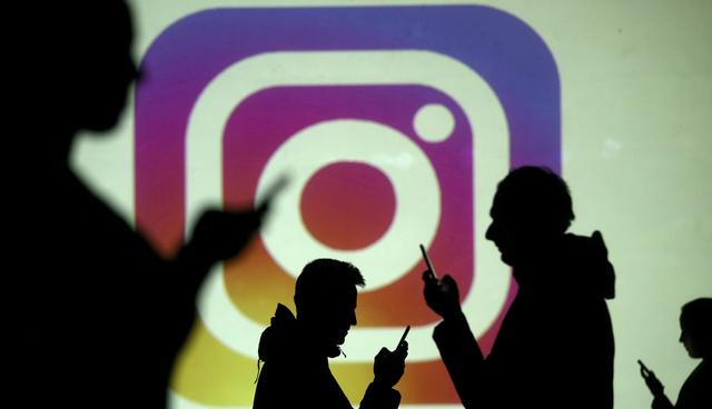 FILE PHOTO: Silhouettes of mobile users are seen next to a screen projection of the Instagram logo in this picture illustration taken March 28, 2018.  REUTERS/Dado Ruvic/Illustration