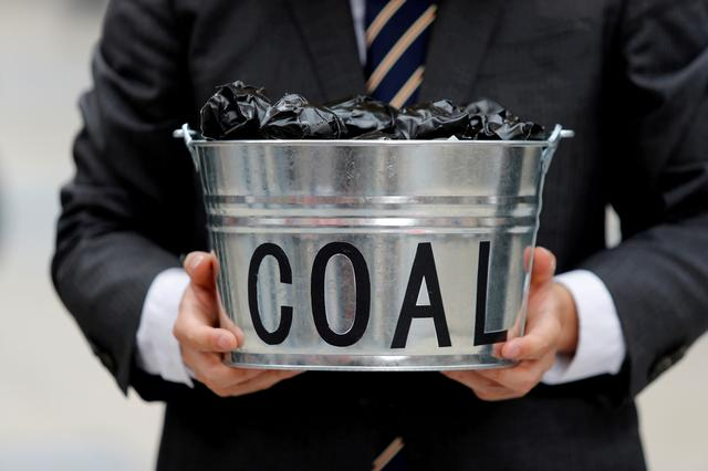 FILE PHOTO: A protester holds a bucket of coal during a demonstration demanding Japan to stop supporting coal at home and overseas, at the G20 Summit in Osaka, Japan, June 28, 2019. REUTERS/Jorge Silva/File Photo
