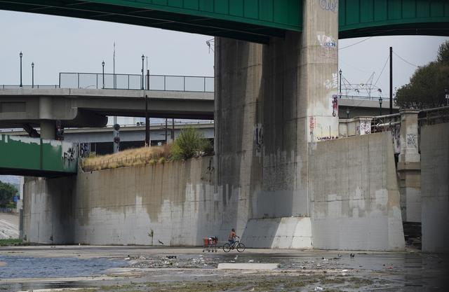 FILE PHOTO: A man experiencing homelessness pulls a shopping cart on his bicycle in the Los Angeles River in Los Angeles, California, U.S. August 11, 2021. REUTERS/Bing Guan