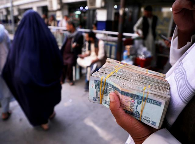 FILE PHOTO: A person holds a bundle of Afghan afghani banknotes at a money exchange market, following banks and markets reopening after the Taliban took over in Kabul, Afghanistan, September 4, 2021. REUTERS/Stringer/File Photo