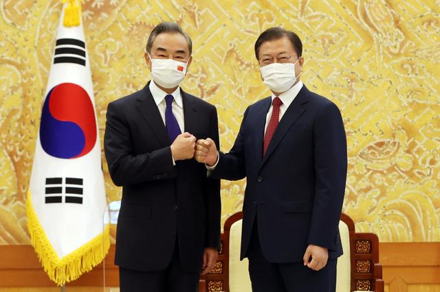 South Korean President Moon Jae-in and Chinese Foreign Minister Wang Yi pose for photographs during their meeting at the Presidential Blue House in Seoul, South Korea, September 15, 2021.   Yonhap via REUTERS