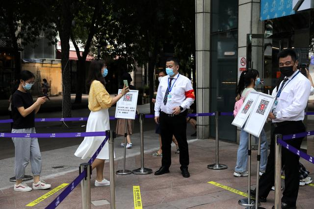 FILE PHOTO: A woman shows her health status on a phone to a security guard, at an entrance of a shopping mall in Beijing, China August 23, 2021. REUTERS/Tingshu Wang/File Photo