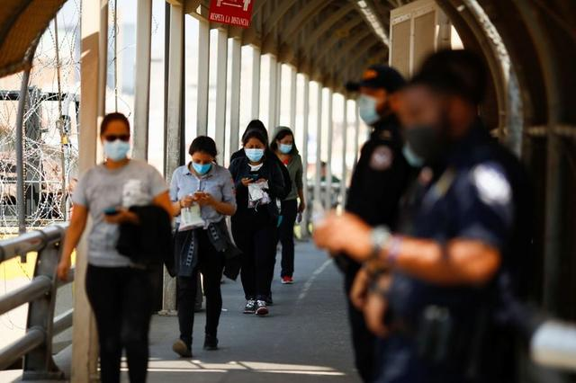 FILE PHOTO: Migrants expelled from the U.S. and sent back to Mexico under Title 42 walk towards Mexico at the Paso del Norte International border bridge, in this picture taken from Ciudad Juarez, Mexico September 9, 2021. REUTERS/Jose Luis Gonzalez
